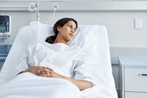 Thoughtful Woman Patient Lying in Hospital Bed